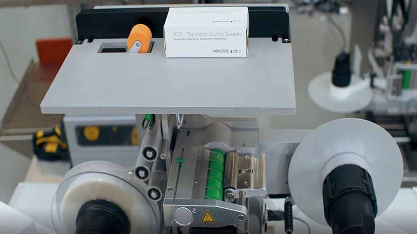 Semi-automatic label dispenser for folding boxes and cartons